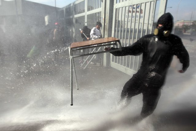 A protester is drenched with water from a water cannon operated by police during clashes in the courtyard of the University of Santiago, during a demonstration in Santiago, Chile, Thursday, April 16, 2015. (Photo by Luis Hidalgo/AP Photo)
