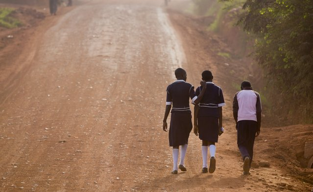 Ugandan children walk up a dusty murram road to school in the morning on the first day of the new term, in Kasangati, near Kampala, in Uganda Monday, February 22, 2016. The new term started later than usual due to the recent presidential elections. (Photo by Ben Curtis/AP Photo)