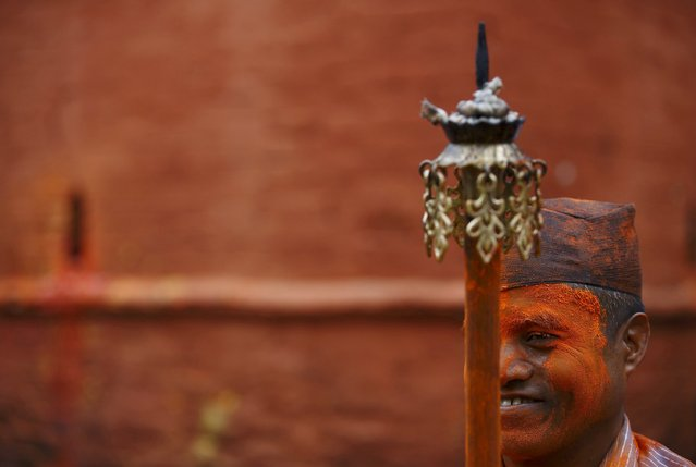 """A devotee smeared in vermillion powder smiles as he holds a """"Chirag"""", traditional lamp, while celebrating the Sindoor Jatra vermillion powder festival at Thimi, in Bhaktapur April 15, 2015. (Photo by Navesh Chitrakar/Reuters)"""