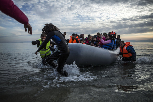 Refugees and migrants are helped by volunteers on their arrival aboard a dinghy at Mytilene on the northeastern Greek island of Lesbos, Tuesday, February 23, 2016. Nearly 100,000 migrants and refugees have traveled to Greek islands from nearby Turkey so far this year. (Photo by Manu Brabo/AP Photo)
