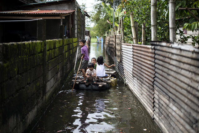 Children use a raft to cross a flooded alley in the aftermath of Super Typhoon Mangkhut in Calumpit, Bulacan on September 16, 2018. (Photo by Noel Celis/AFP Photo)