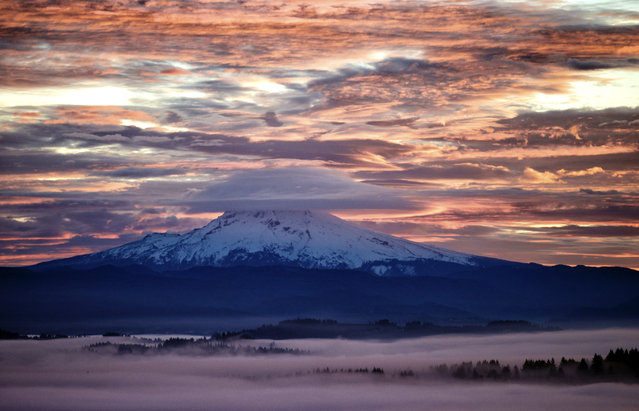 Fog settles low over Happy Valley as a lenticular cloud obscures the summit of Mount Hood as the sunrise lights up wispy clouds, Thursday, January 2, 2014, in a view looking north from Mount Scott, Ore. (Photo by Thomas Boyd/AP Photo/The Oregonian)