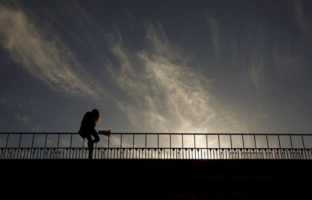 A woman sits on a guardrail as she checks her phone during sunset in a park in Madrid April 7, 2015. (Photo by Sergio Perez/Reuters)