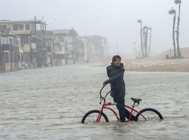 Jake Hart, 13, plays in the rising floodwater during a storm in Seal Beach, Calif., Sunday, January 22, 2017. The heavy downpour on Sunday drenched Orange County in one of the heaviest storms of the year. Fast-moving floodwaters swept through California mountain communities and residents fled homes below hillsides scarred by wildfires as the third in the latest series of storms brought a deluge Sunday and warnings about damaging mudslides. (Photo by Ana Venegas/The Orange County Register via AP Photo)