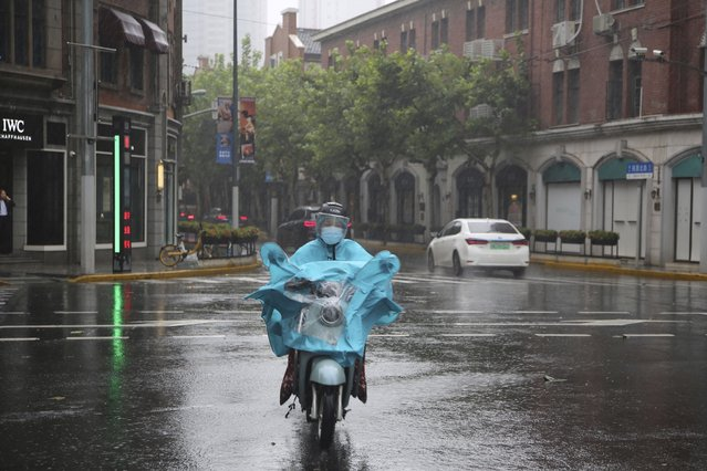 A resident wearing a mask and rain gear rides on the street as it rains in Shanghai, China, Monday, September 13, 2021. (Photo by Chen Si/AP Photo)