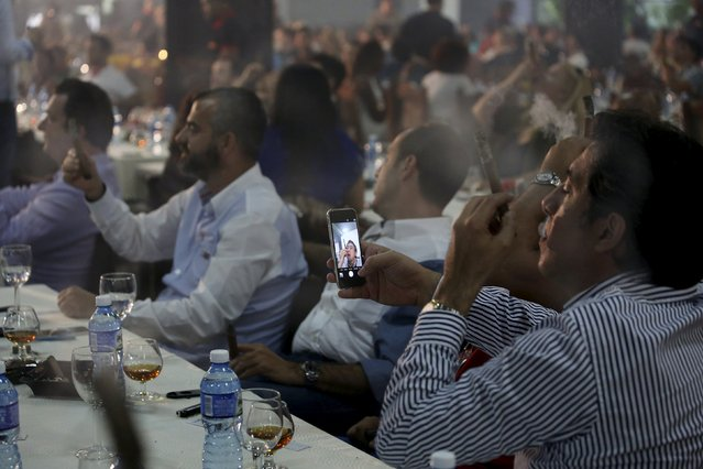 A competitor takes a selfie as he competes for the longest ash during the XVIII Habanos Festival in Havana, March 3, 2016. (Photo by Alexandre Meneghini/Reuters)