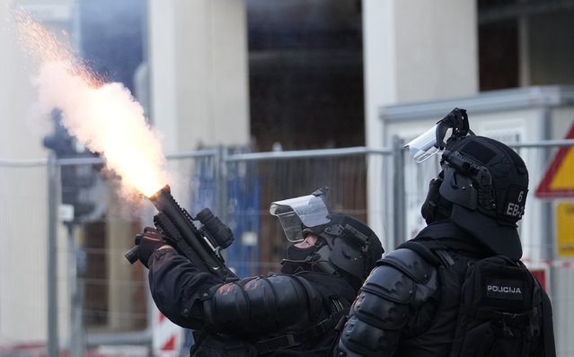 Police fire tear gas during a protest against vaccinations and coronavirus measures in Ljubljana, Slovenia, Tuesday, October 5, 2021. EU leaders are meeting Tuesday evening in nearby Kranj, Slovenia, to discuss increasingly tense relations with China and the security implications of the chaotic U.S.-led exit from Afghanistan, before taking part in a summit with Balkans leaders on Wednesday. (Photo by Petr David Josek/AP Photo)