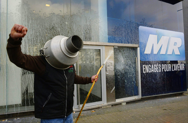 A farmer sprays milk on the frontage of the headquarter of the belgian right wing liberal party Mouvement Reformateur (MR) during a demonstration in Brussels on March 14, 2016. The European Union voiced support on March 14 for temporary cuts in milk production by farmers in member states in a bid to reverse the plunge in prices that has shaken the dairy industry. (Photo by John Thys/AFP Photo)