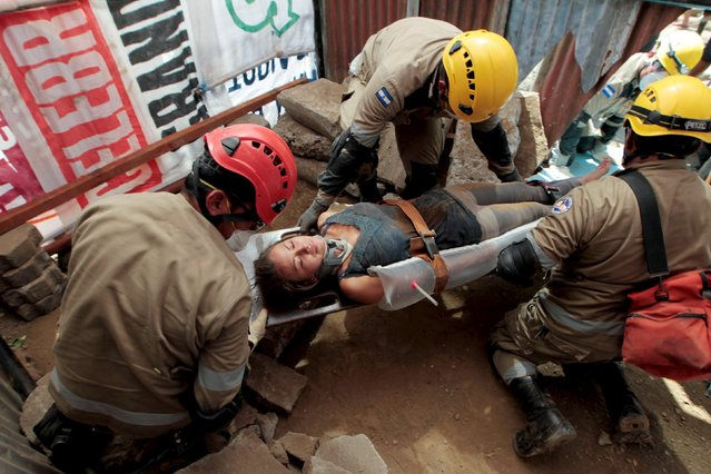 A woman playing the role of an injured person is attended by members of the rescue unit of the army of Nicaragua, during an earthquake drill in Managua, Nicaragua March 17, 2016. (Photo by Oswaldo Rivas/Reuters)