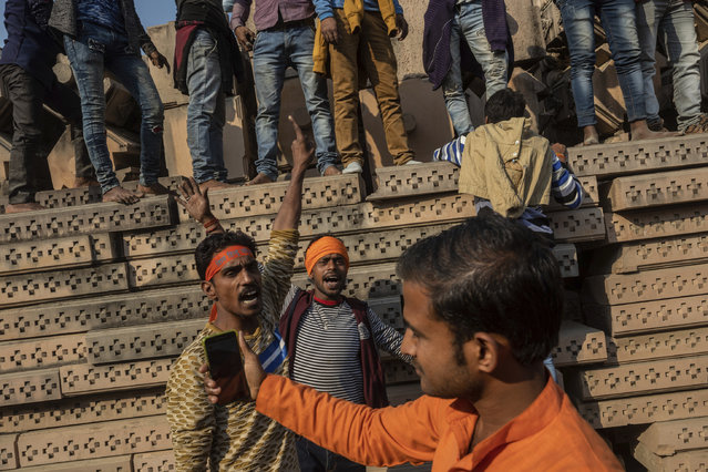 In this Sunday, November 25, 2018 photo, Hindu hardliners gather next to building materials to be assembled in a temple dedicated to Hindu god Ram in Ayodhya, Uttar Pradesh, India. (Photo by Bernat Armangue/AP Photo)