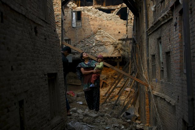A woman carrying her child stands in an alley surrounded by damaged and collapsed houses following April 25 earthquake at Bhaktapur May 7, 2015. (Photo by Navesh Chitrakar/Reuters)