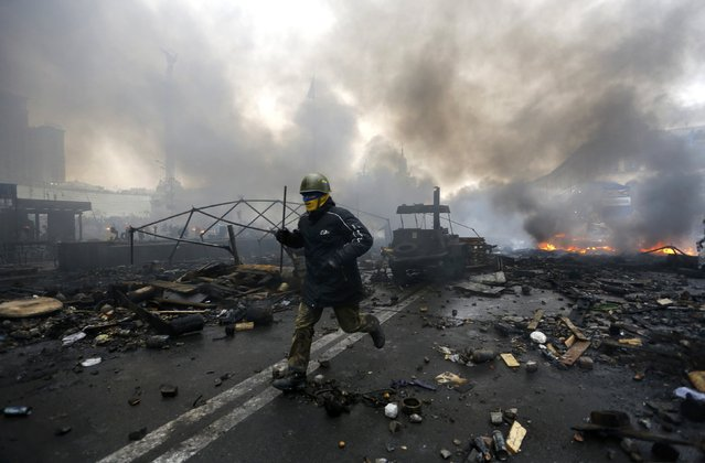 An anti-government protester runs trough the rubble after violence erupted in the Independence Square in Kiev February 20, 2014. (Photo by Yannis Behrakis/Reuters)