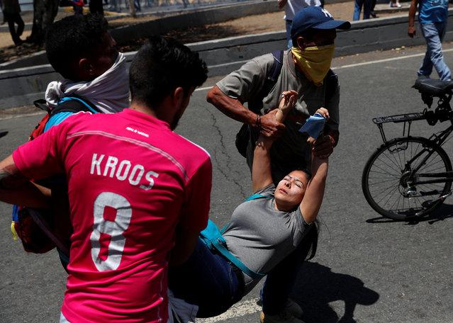 "Opposition demonstrators help an injured fellow near the Generalisimo Francisco de Miranda Airbase ""La Carlota"", in Caracas, Venezuela April 30, 2019. (Photo by Carlos Garcia Rawlin/Reuters)"