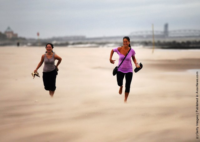 Women run along a sand-swept beach at Coney Island following heavy rain and winds from Hurricane Irene