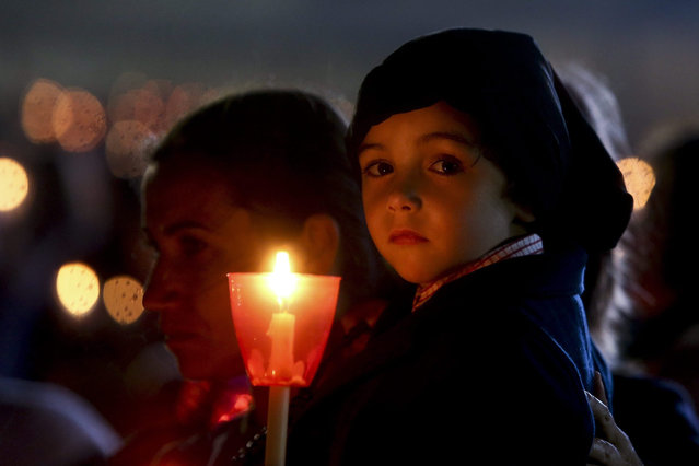 A child holds a candle in the Candles Procession during the annual 13th May pilgrimage to Fatima Sanctuary, Fátima, Portugal, 12 May 2015. (Photo by Paulo Novais/EPA)
