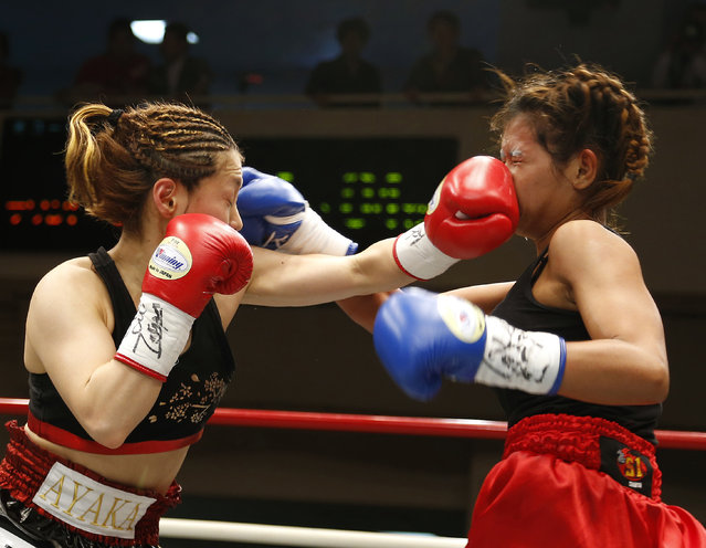 Japanese champion Ayaka Miyao, left, hits a left to the face of Thai challenger Buangern Onesongchai Gym in the second round of their WBA light minimumweight women's boxing title bout in Tokyo, Monday, March 3, 2014. Miyao defended her title with a knockout in the fifth round. (Photo by Toru Takahashi/AP Photo)