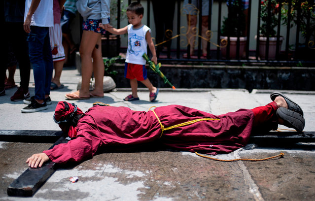 A Christian devotee lies on a cross on a street in Mabalacat, Pampanga on April 18, 2019, one day ahead of the reenactment of the crucifixion of Jesus Christ on Good Friday. (Photo by Noel Celis/AFP Photo)