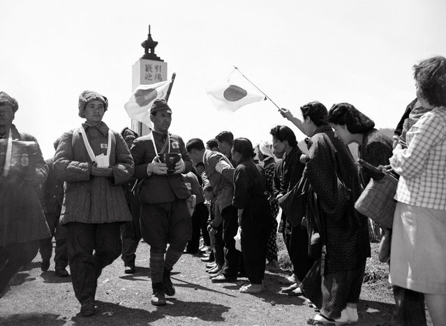 Women greet repatriated Japanese soldiers, formerly prisoners of war, on April 26, 1950. The men bear the ashes of their friends who died during their imprisonment. (Photo by AP Photo via The Atlantic)