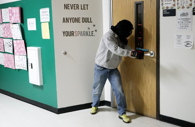 A student prepares to search a classroom in a middle school for a shooter during an Active Shooter Response course offered by TAC ONE Consulting in Denver April 2, 2016. According to TAC ONE, the course, which is offered for the first time to concealed weapons permit carrying civilians, is designed at preparing people to effectively save lives prior to the arrival of law enforcement at an active shooter incident. (Photo by Rick Wilking/Reuters)