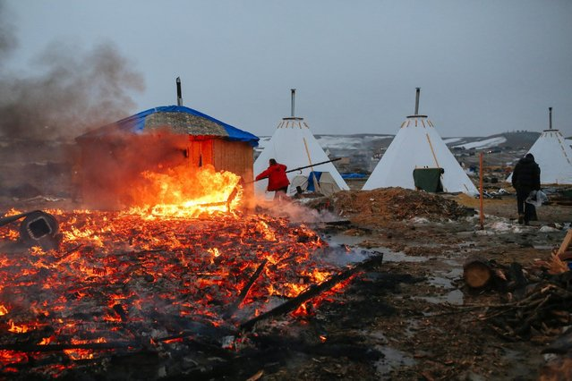 Campers set structures on fire in preparation of the Army Corp's 2pm deadline to leave the Oceti Sakowin protest camp on February 22, 2017 in Cannon Ball, North Dakota. Activists and protesters have occupied the Standing Rock Sioux reservation for months in opposotion to the completion of the Dakota Access Pipeline. (Photo by Stephen Yang/Getty Images)
