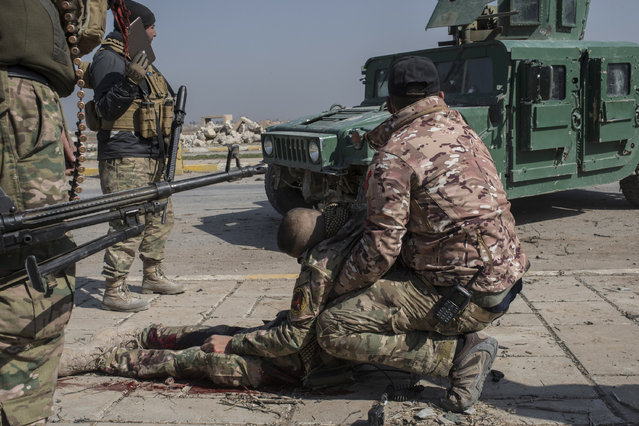An injured Iraqi Emergency Response Division (ERD) soldier hit by a mortar is held by another officer as they wait for medics to arrive at the Islamic State occupied Mosul Airport in west Mosul, part of the offensive to retake the city some two years after it fell to the hardline jihadist group, February 23, 2017. Iraqi forces encountered stiff resistance with improvised explosives, heavy mortar fire and snipers hampering their advance before they successfully took the airport. (Photo by Martyn Aim/Getty Images)