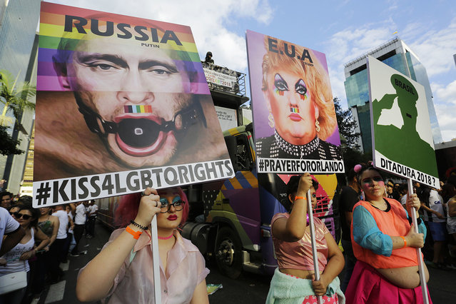 Revelers holds posters depicting United States President Donald Trump, and Russian President Vladimir Putin, left, as they march during the annual Gay Pride Parade in Sao Paulo, Brazil, June 18, 2017. (Photo by Nelson Antoine/AP Photo)