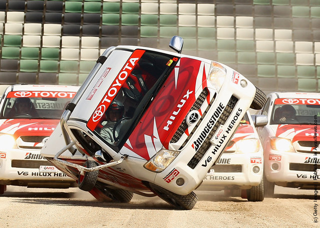 A car is driven on two wheels by the team from Toyota V6 HiLux Heroes during a Royal Melbourne Show