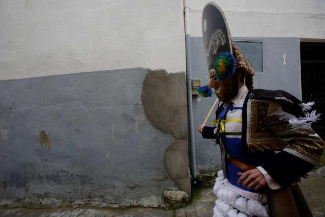 """A carnival reveller dressed as a """"Peliqueiro"""" runs along a street in the village of Laza, Spain February 26, 2017. (Photo by Miguel Vidal/Reuters)"""