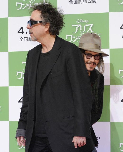 "Mr Depp hides behind film director Tim Burton as they promote ""Alice in Wonderland"" in Tokyo, 2010. (Photo by Yoshikazu Tsuno/AFP Photo)"