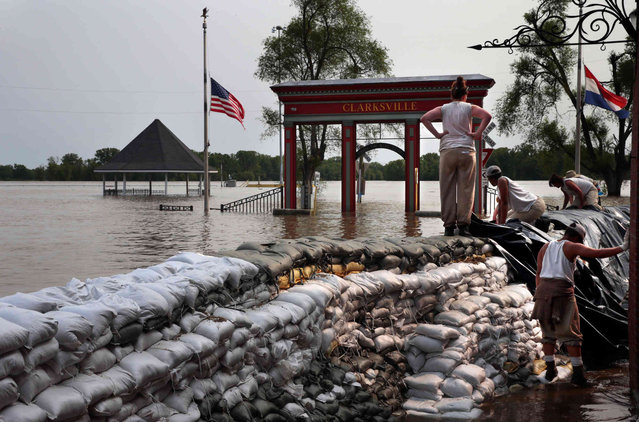 Inmates from the Women's Eastern Reception Diagnostic and Correctional Center in Vandalia, Mo., watch the Mississippi River after helping to raise a sandbag wall in Clarksville as the river approaches record levels downtown on Friday, May 31, 2019. (Photo by Robert Cohen/St. Louis Post-Dispatch via AP Photo)