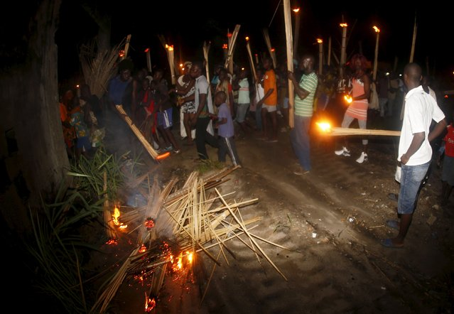 Participants walk through the street with fire torches during the Generation Festival in Moossou May 22, 2015. The festival is held every year by the Aboure, an ethnic group living in southern Ivory Coast, as a way to introduce the next generation that will participate in the ruling of the village. (Photo by Thierry Gouegnon/Reuters)