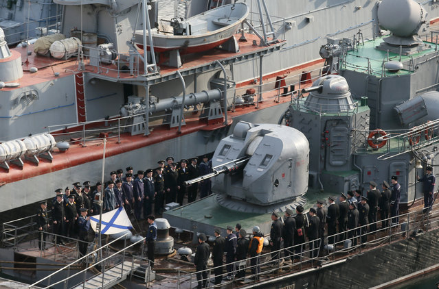 "Russian navy sailors stand still during a flag-raising ceremony at the deck of  ""Suzdalets"" (IPC-118) – small ASW ship project 1124 M moored in the bay of the Crimean city of Sevastopol, Ukraine, March 26, 2014. The previous day, Russian President Putin ordered Russian administration be put into place in newly annexed Crimea by the end of the week. (Photo by Sergei Ilnitsky/EPA)"