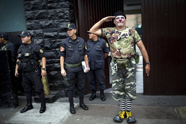 A clown dressed as a soldier performs at the main entrance of a police station during a march commemorating the Peruvian clown day in Lima Peru, Monday, May 25, 2015. (Photo by Rodrigo Abd/AP Photo)
