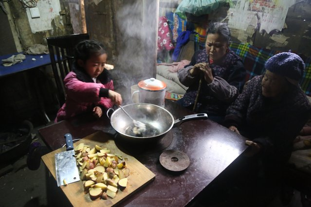 5-year-old Chinese girl Wang Anna feeds her great-grandmother at home in Zhuyuan village, Guizhou province, China on March 3, 2017. (Photo by Imaginechina/Rex Features/Shutterstock)