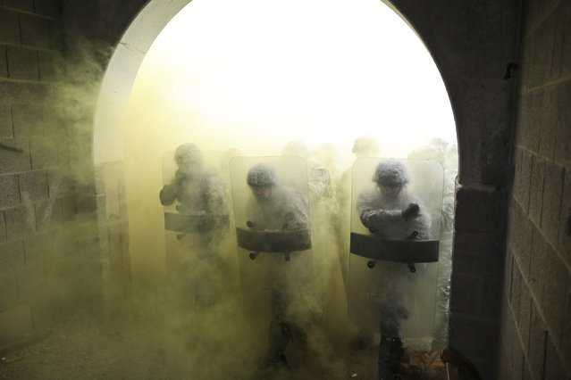 U.S. soldiers with the 525th Battlefield Surveillance Brigade advance through a tunnel while conducting riot control operations during a Kosovo Force (KFOR) mission rehearsal exercise (MRE) at the Joint Multinational Readiness Center in Hohenfels, Germany, May 12, 2013. The KFOR 17 MRE was designed to prepare the U.S. Army's 525th Battlefield Surveillance Brigade for operations in support of NATO in Kosovo. (Photo by Spc. Bryan Rankin/HHC Operations Group)