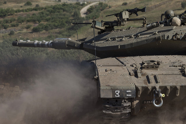An Israeli tank moves into position in the Israeli controlled Golan Heights during fighting between forces loyal to Syrian President Bashar Assad and rebels in the Druze village of Khader in Syria, Tuesday, June 16, 2015. As many as 20 members of the Druze minority sect were killed last week, the deadliest violence against the Druze since Syria's conflict started in March 2011, sparking fears of a massacre against the sect. (AP Photo/Ariel Schalit)