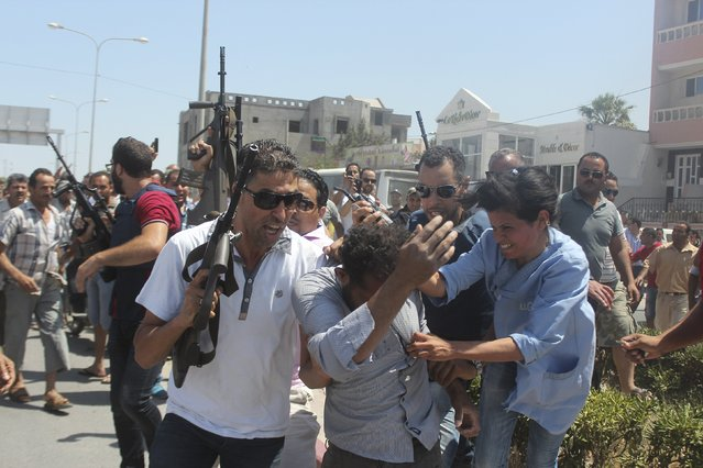 Police officers control the crowd (rear) while surrounding a man (front C) suspected to be involved in opening fire on a beachside hotel in Sousse, Tunisia, as a woman reacts (R), June 26, 2015. At least 27 people, including foreign tourists, were killed when at least one gunman opened fire on a Tunisian beachside hotel in the popular resort of Sousse on Friday, an interior ministry spokesman said. (Photo by Amine Ben Aziza/Reuters)