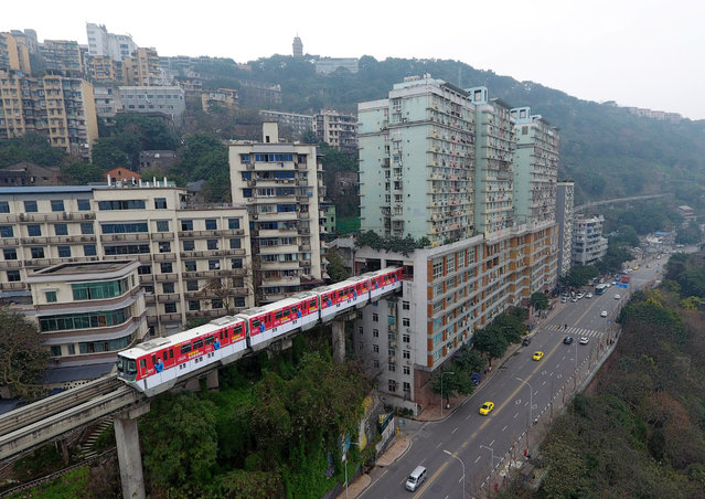 A light railway train passes through a residential building on March 18, 2017 in Chongqing, China. Chongqing Rail Transit No.2 and a 19-storey residential building have been built across each other. The railway set its Liziba Station on the sixth to eighth floor in the building with noise reduction equipment. (Photo by VCG/VCG via Getty Images)