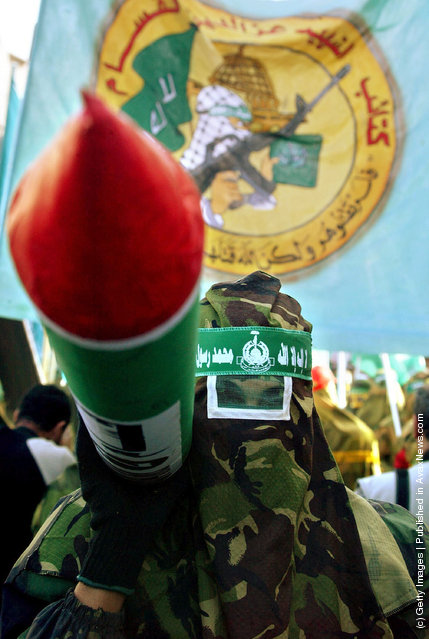 Palestinian youths look at masked members of Ez Al Dine Al Qassam, a militia linked to HAMAS