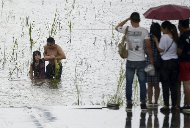 A man grabs the arm of a woman, who attempted to commit suicide by jumping into the Yangtze River, as they walk onto the banks, in Wuhan, Hubei province, China, June 27, 2015. The man, surnamed Liu, jumped into the river soon after seeing the suicide attempt. He managed to rescue the woman. The reason of the suicide remained unknown, local media reported. (Photo by Reuters/Stringer)