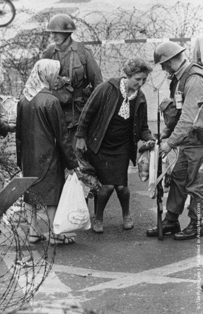 1969:  British troops search a woman's shopping at a check point in the Falls Road area of Belfast