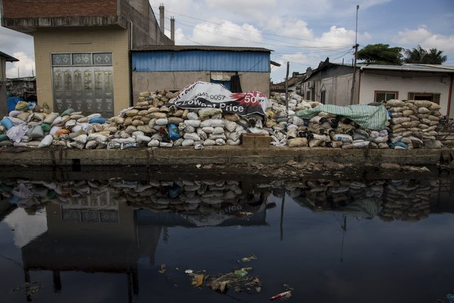 A polluted river flows past a workshop used for processsing plastic components of electronic waste at the township of Guiyu in China's southern Guangdong province June 10, 2015. (Photo by Tyrone Siu/Reuters)