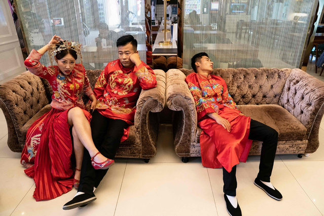 This picture taken on June 25, 2019 shows couples wait for their turn for their pre-wedding photo shoot at the Love Story in Rome Studio in Beijing. Increasingly elaborate pre-wedding photos are a booming industry in China, as young couples spend time and cash lining up glamorous photo shoots to display on their big day. (Photo by Fred Dufour/AFP Photo)