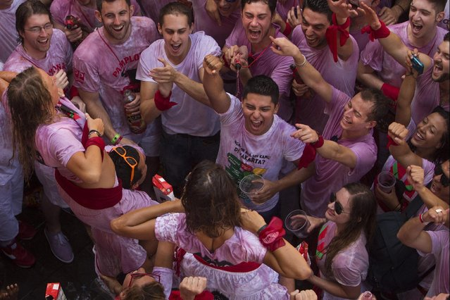 """Revelers shout as girls pull up their t-shirts during the launch of the """"Chupinazo"""" rocket, to celebrate the official opening of the 2015 San Fermin festival in Pamplona, Spain, Monday, July 6, 2015. (Photo by Andres Kudacki/AP Photo)"""
