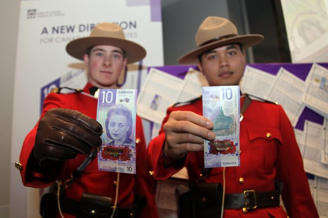 Two police officers show the new vertical $10 notes featuring Viola Desmond, who helped start the modern civil rights movement in Canada, on November 19, 2018 in Toronto, Canada. Canada issued the first vertical $10 note in Toronto on Monday. (Photo by Yu Ruidong/China News Service/VCG via Getty Images)