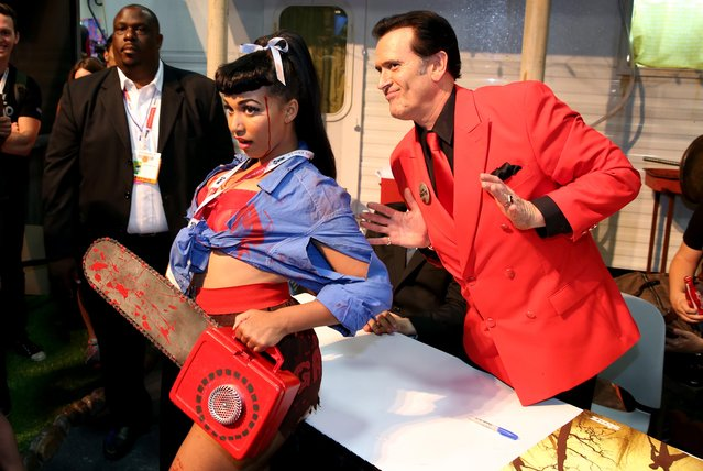 """Bruce Campbell, right, poses with a fan during an autograph signing for the STARZ original series """"Ash vs Evil Dead"""" at San Diego Comic-Con on Friday, July 10, 2015 in San Diego. (Photo by Matt Sayles/Invision for STARZ/AP Images)"""