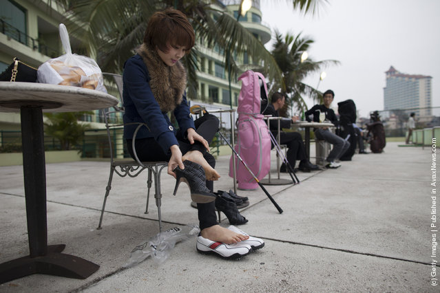 A woman takes her high heels off to  get ready to practice driving the balls at the Hanoi club golf center