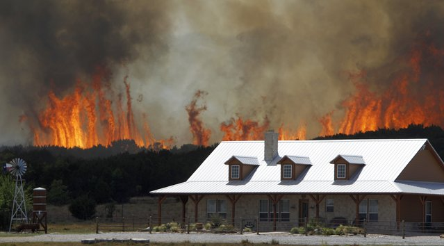 "In this April 19, 2011 file photo, a wildfire threatens a house near Possum Kingdom, Texas. Global warming is rapidly turning America the beautiful into America the stormy, sneezy and dangerous, according to a new federal scientific report released Tuesday, May 6, 2014.  The report emphasizes how warming and its all-too-wild weather are changing daily lives, even using the phrase ""climate disruption"" as another way of saying global warming. (Photo by L. M. Otero/AP Photo)"