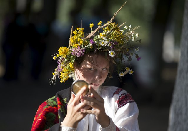 "A Belarussian woman looks in the mirror as she takes part in the festival of national traditions ""Piatrovski"" in the village of Shipilovichi, south of Minsk, July 12, 2015. (Photo by Vasily Fedosenko/Reuters)"