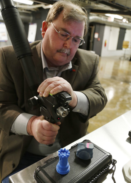 Kevin Collier scans several small models, which can then be digitally manipulated and 3D printed, at America Makes, the National Additive Manufacturing Innovation Institute in Youngstown, Ohio, March 5, 2014. (Photo by Jason Cohn/Reuters)